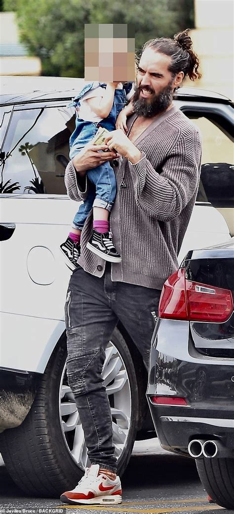 Russell Brand, 43, looks ever the doting dad as he holds